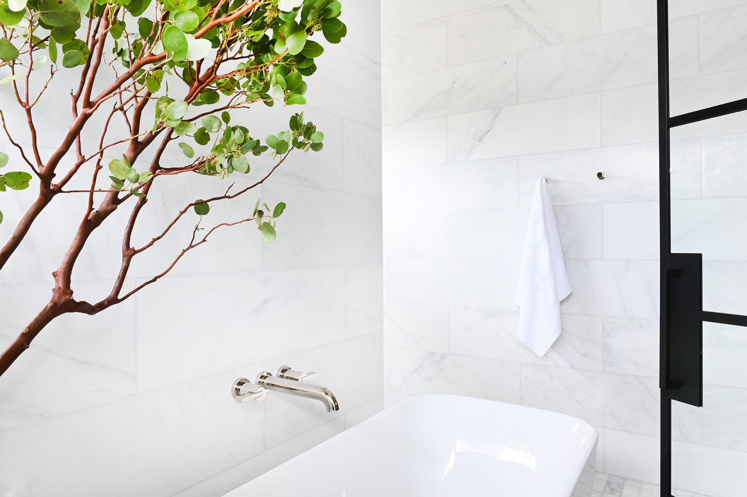 Ferme Moderne bath tub with marble backsplash and green tree designed by Midland Premium Properties in Vancouver, BC