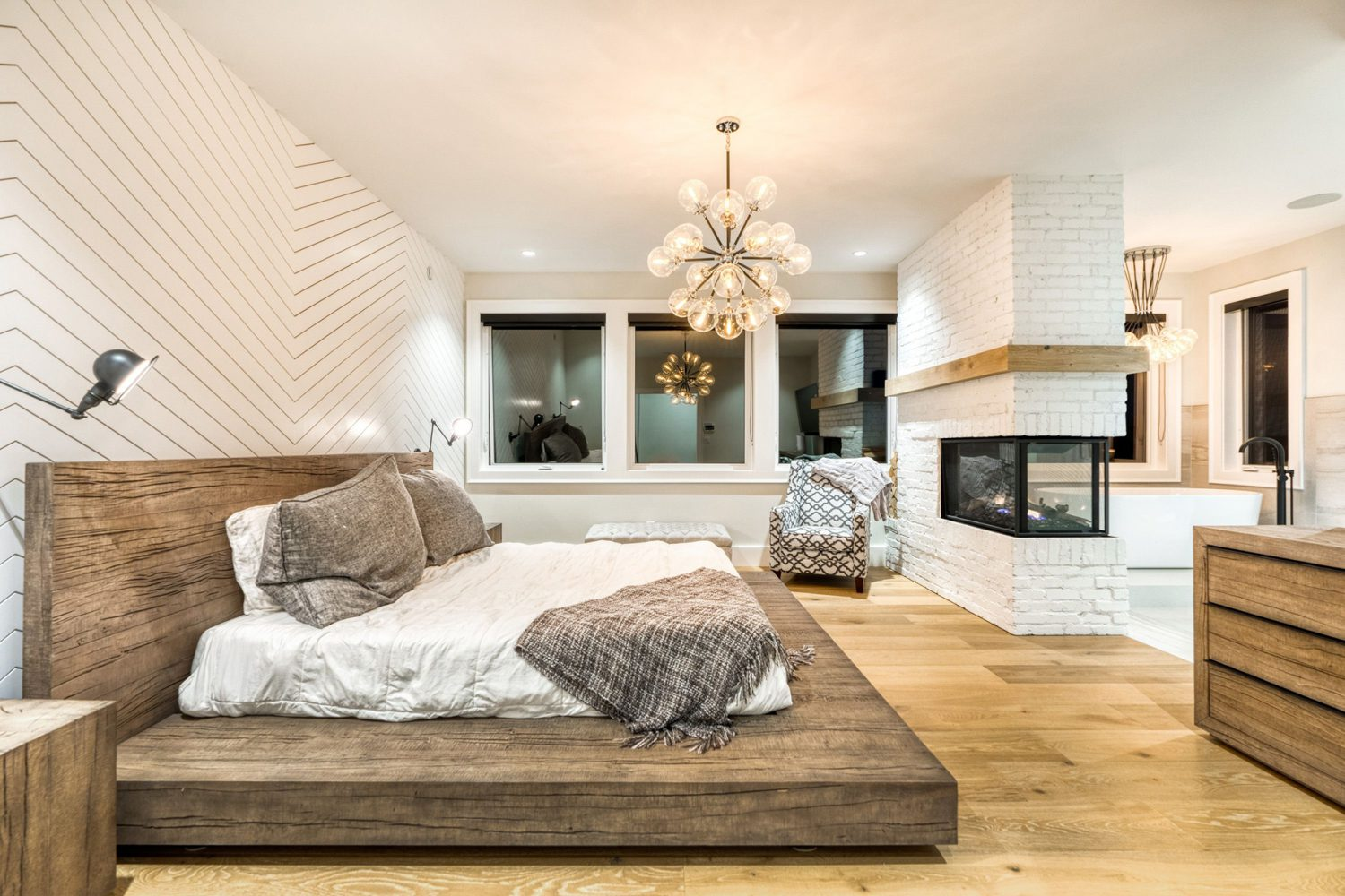 Custom bedroom with king bed, chandelier, fireplace and large windows by Midland Premium Properties in the Greater Vancouver area.