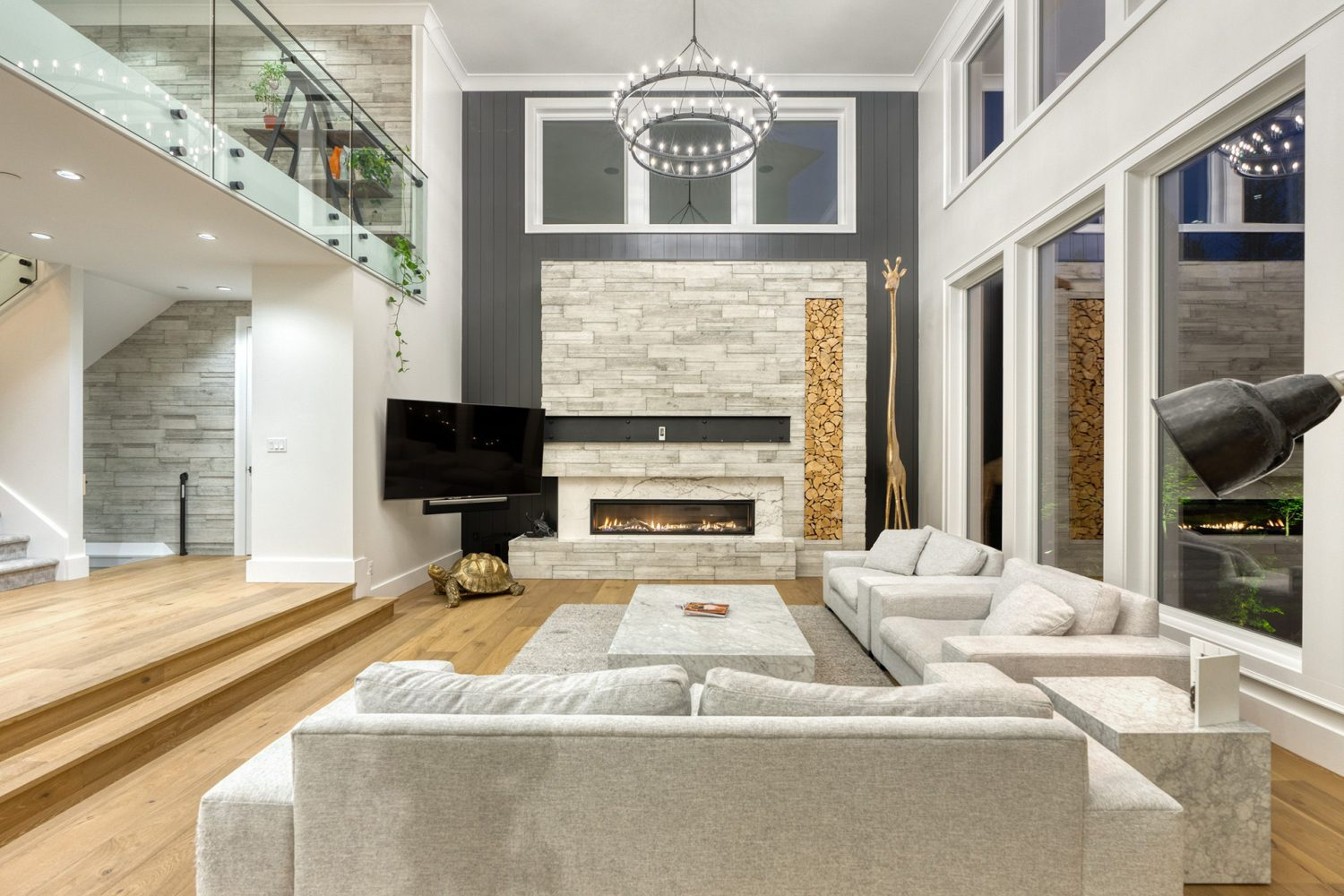 Custom living room with large couches and chandelier by Midland Premium Properties in the Greater Vancouver area.