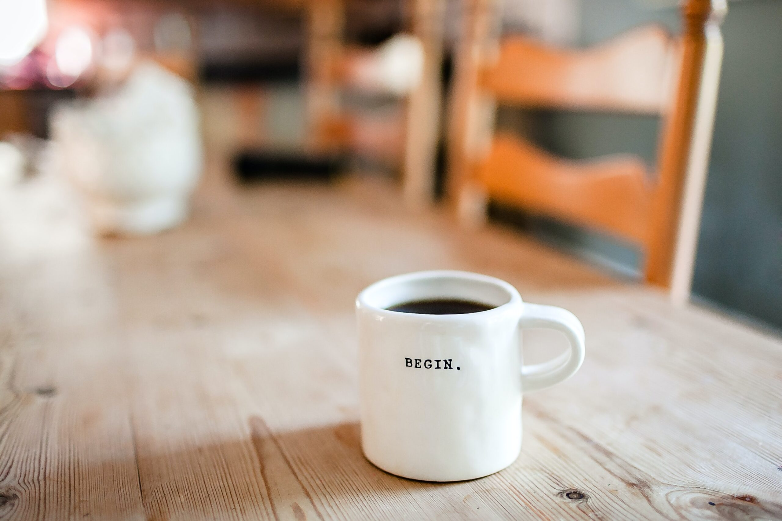 """Coffee cup with the word """"begin"""" on it, sitting on a table"""