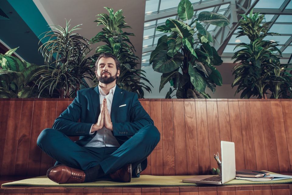 Male worker in suit meditating on bench in office.