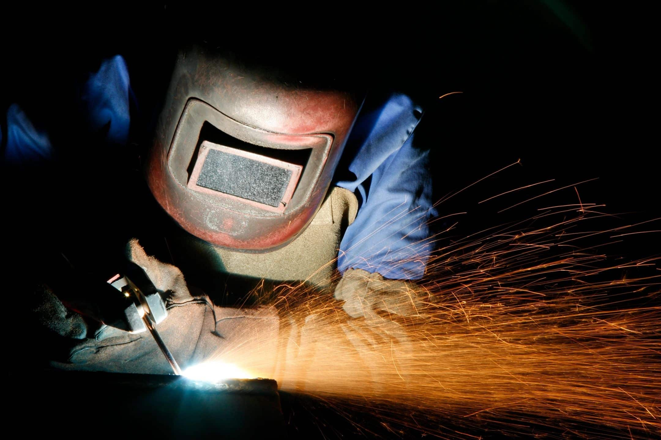 Welder with sparks on metal