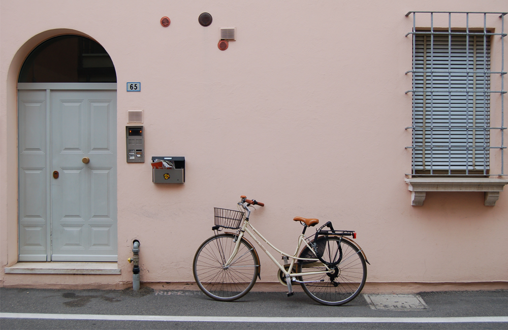 Yellow bicycle with basket in front near handle bard. leaning on a pink wall with a house number of 65 on the wall