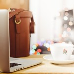 laptop with brown satchell and a cup of coffee