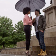 woman in pink shirt and black pants and man in jackets with yellow timberlands standing under a umbrella by a marble statue