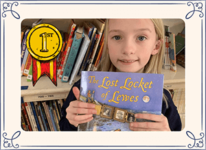 Little girl holding The Lost Locket of Lewes book with first place award