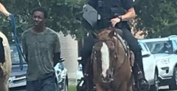 Trump Effect - Black Man on leash being pulled by officer on horse.
