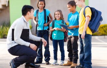 elementary pupils outside classroom talking to teacher