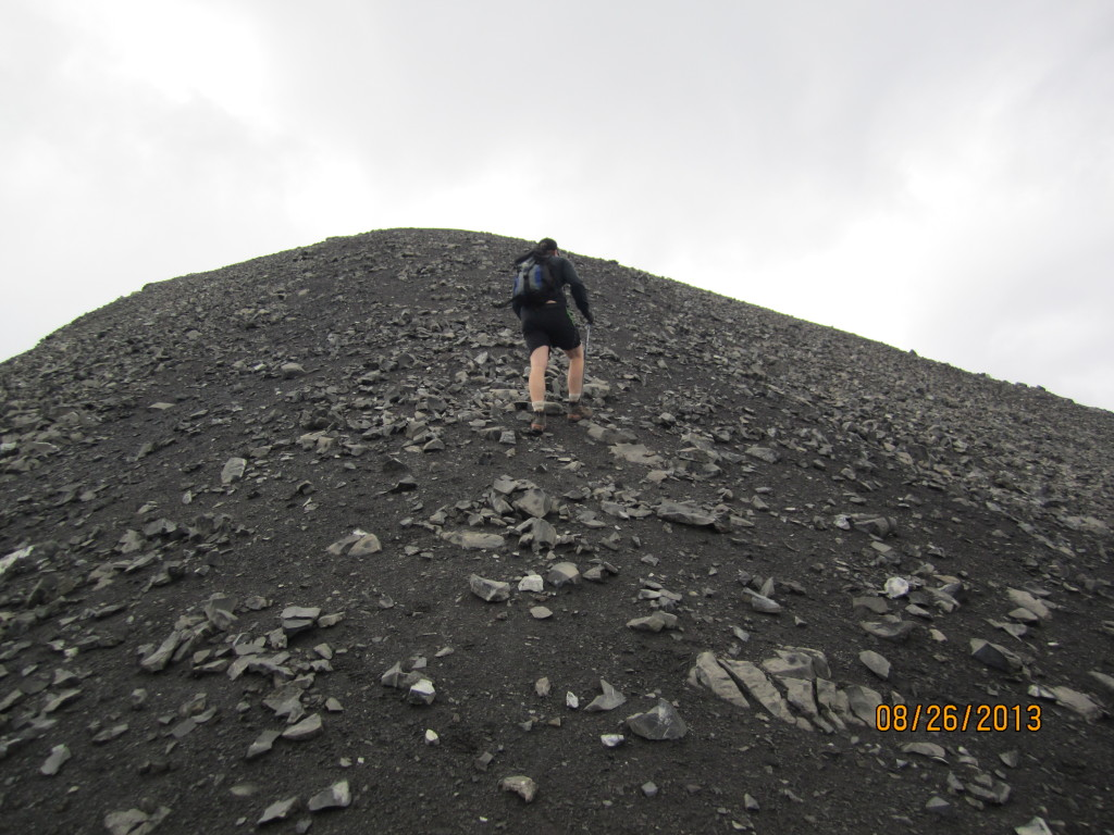 The last few steps on very black dirt to the top