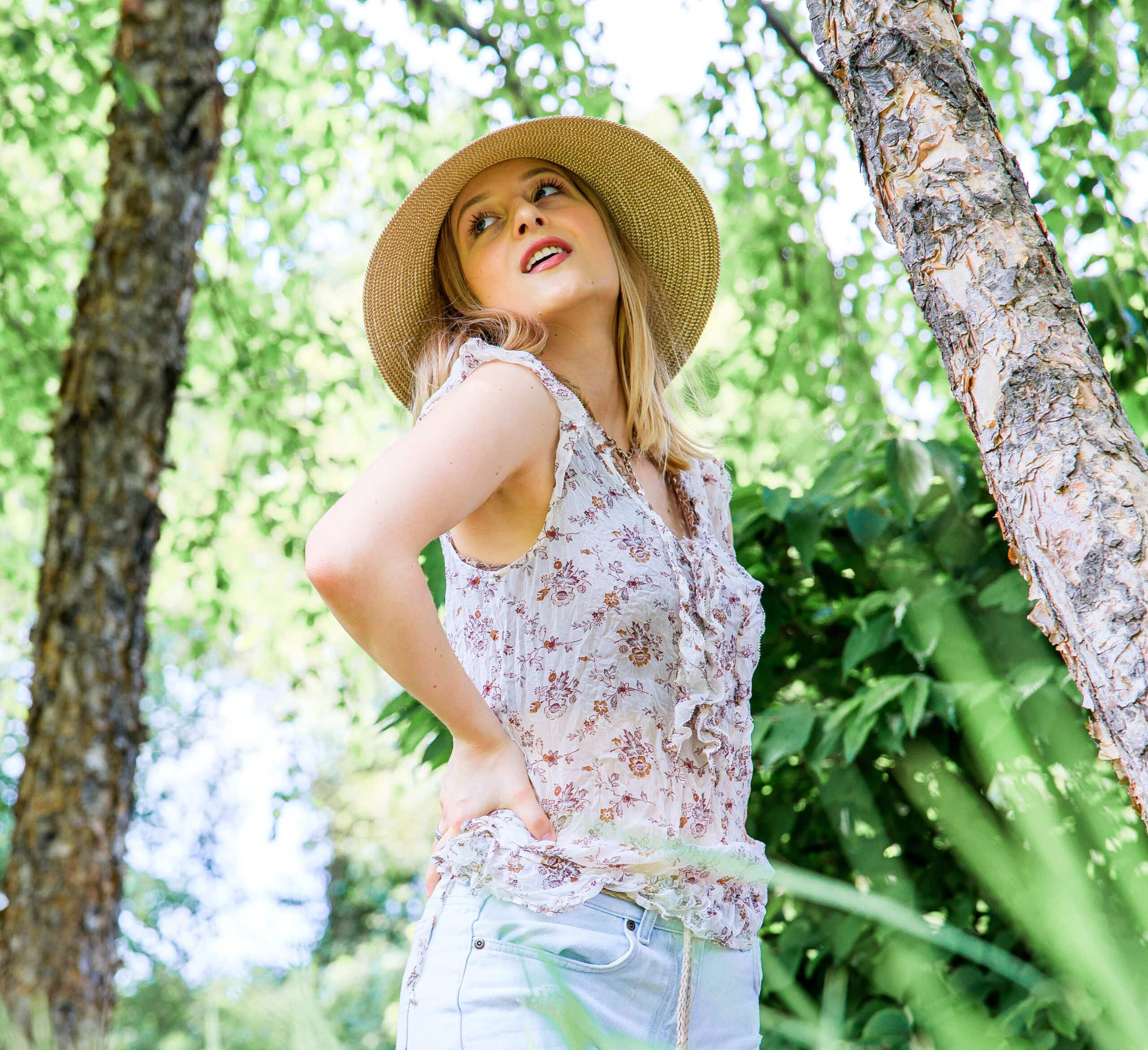 A blonde woman, wearing a hat, looking over her shoulder passed the camera. Portrait taken by Hance Studios in Berkley, Michigan 48072.