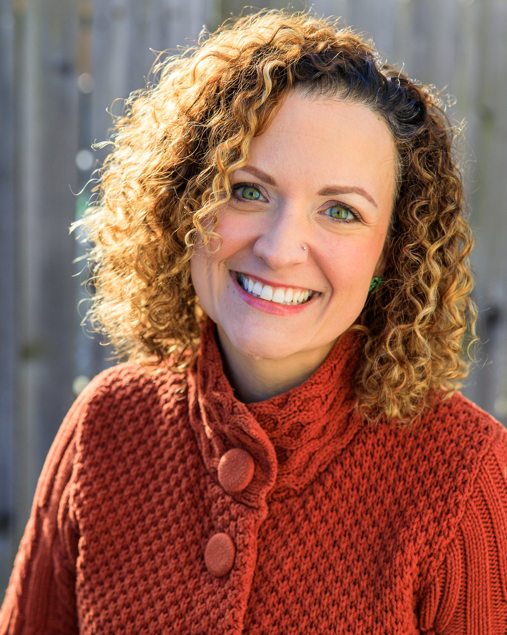 A smiling woman with green eyes, an orange sweater, and curly hair. Portrait taken in Berkley, Michigan 48072.