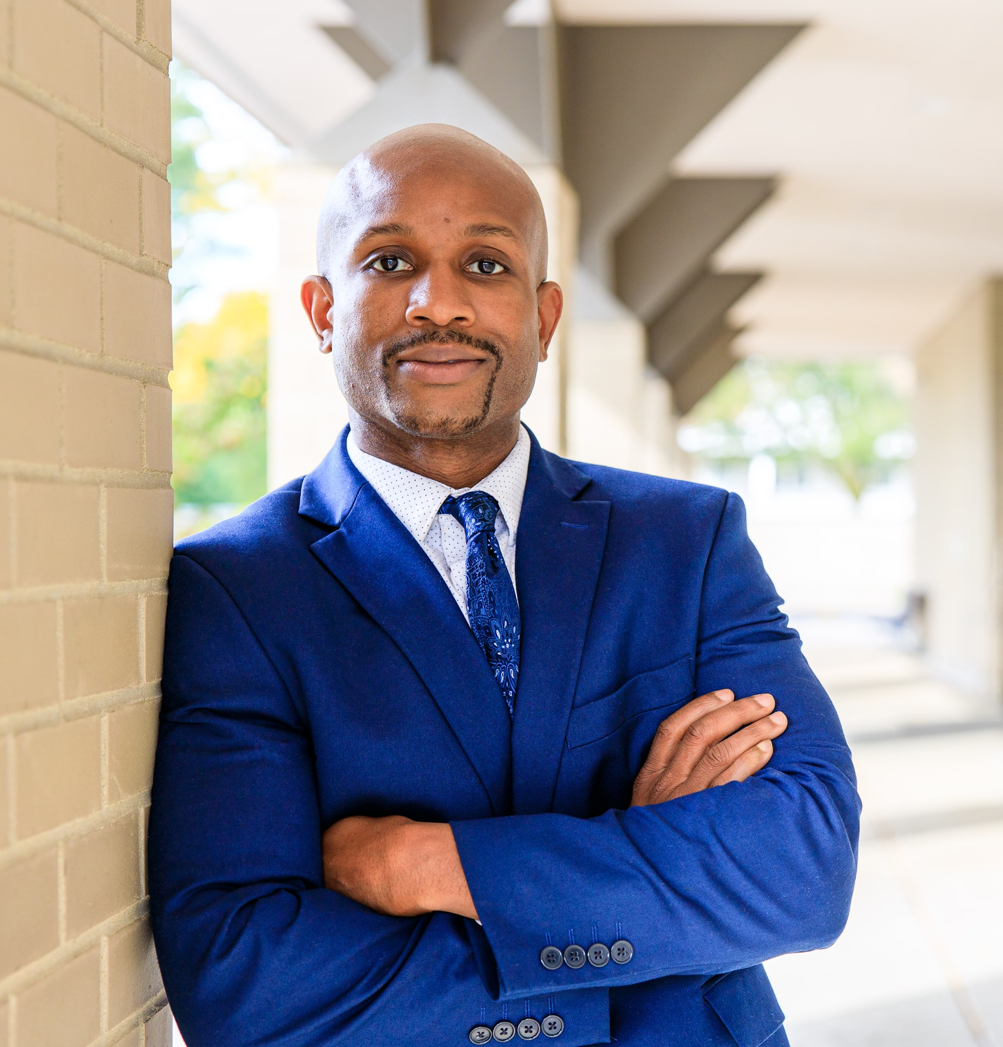 A handsome bald smiling man with brown eyes, wearing a blue business suit, blue tie, white button down, crossing his arms, leaning against a brick column. Portrait taken by Hance Studios in Berkley, Michigan 48072.