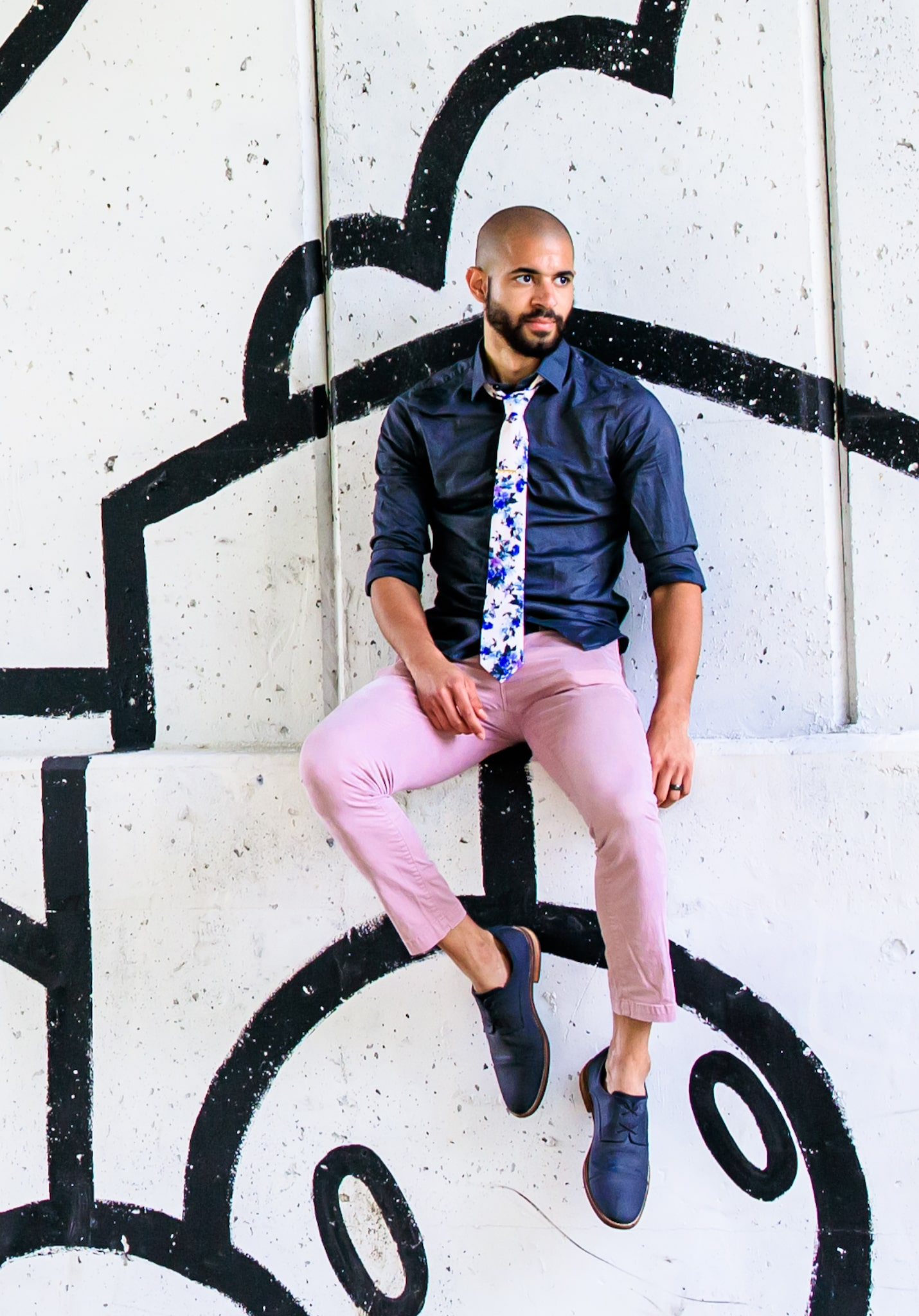 A bald man sitting on a ledge, wearing business casual with a fashion twist of pink pants and colorful tie. Portrait taken by Hance Studios in Berkley, Michigan 48072.