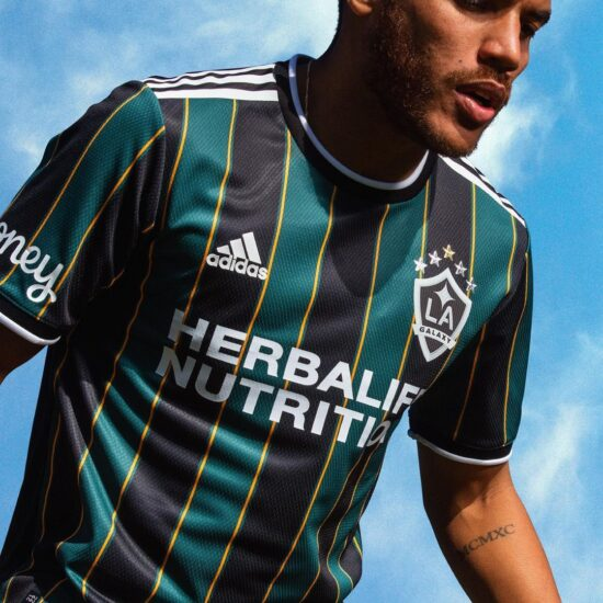Emerald green and black vertical stripes with Herbalife Nutrition written across the chest in white letters