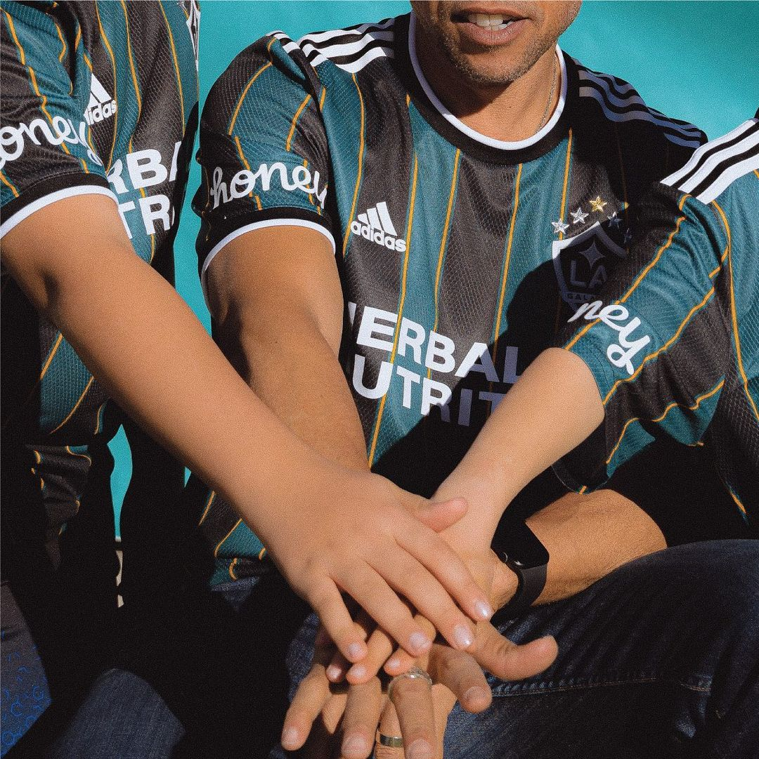 Three people piling their hands on top of each other wearing the new Galaxy jersey