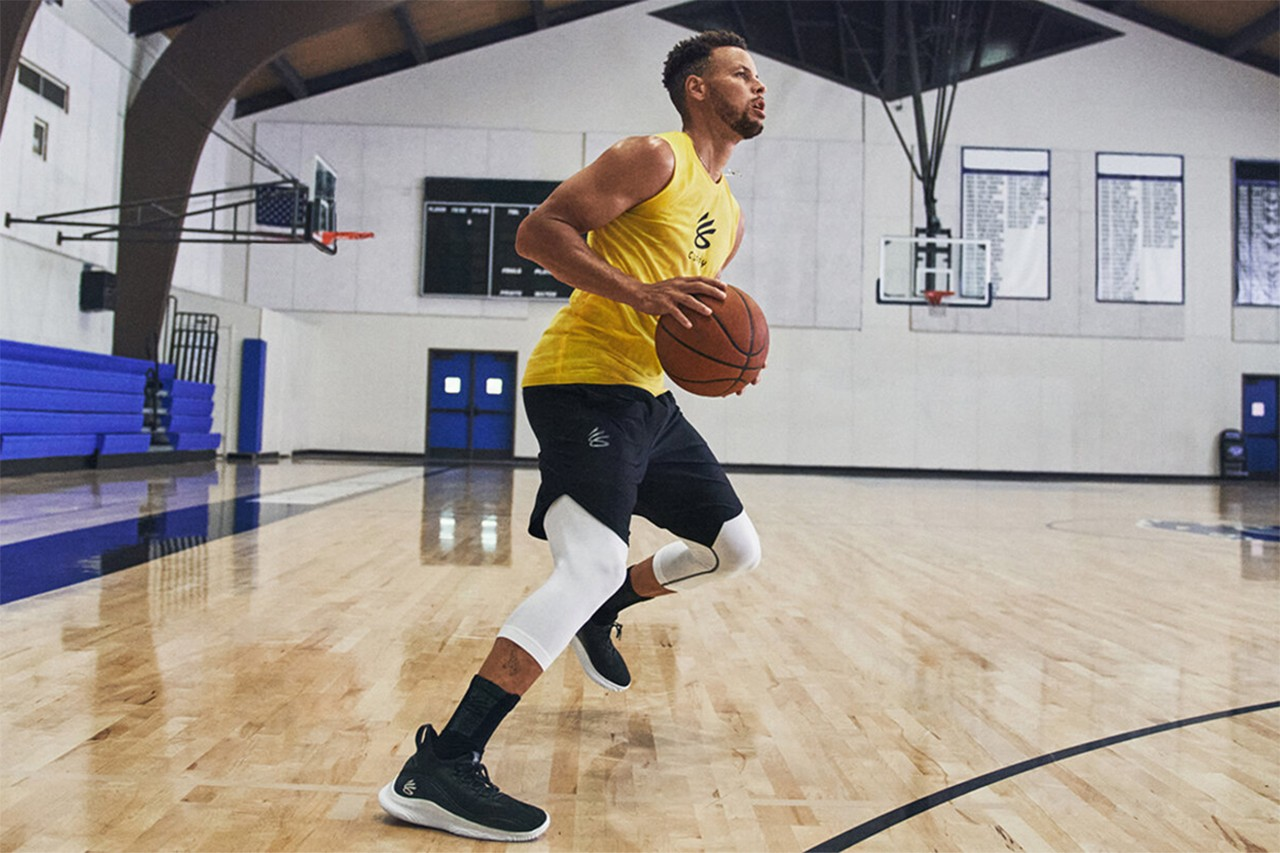 Stephen Curry dribbles a basketball in a gym on a basketball court