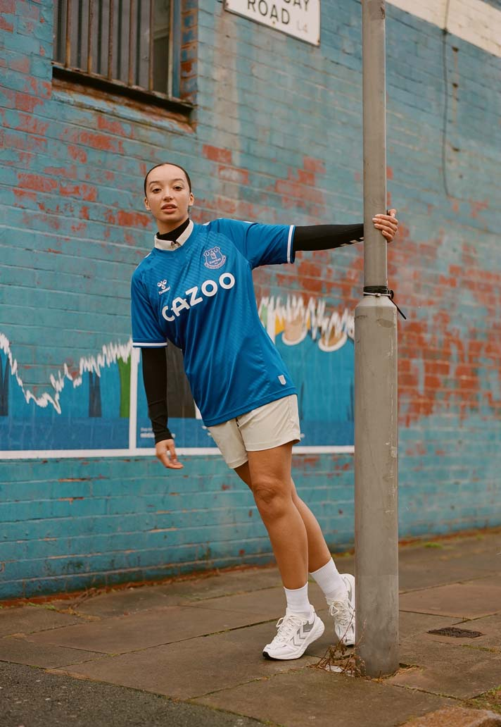 Woman with blue jersey leans from a light pole