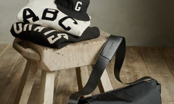 A white sweatshirt is stacked on top a black sweatshirt on a stool with a cap and messenger back next to it