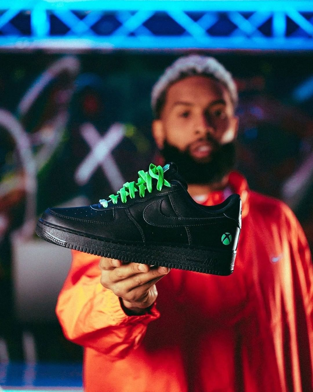 Odell Beckham Jr. holds a solid black sneaker with green laces