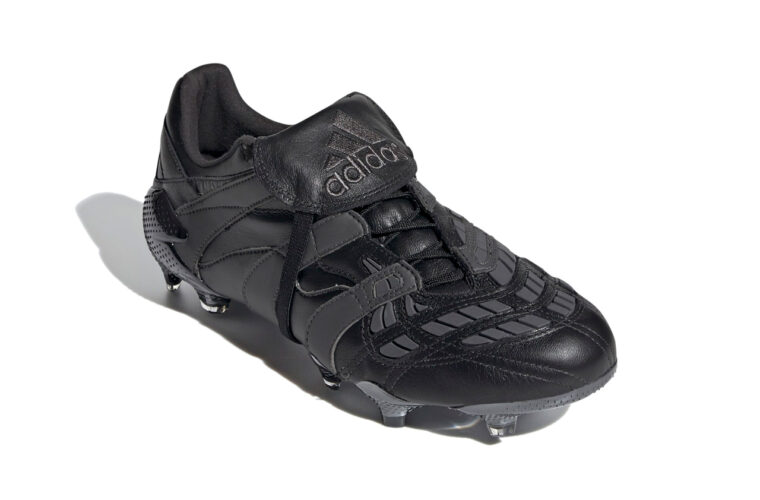 Black football boot with black spikes