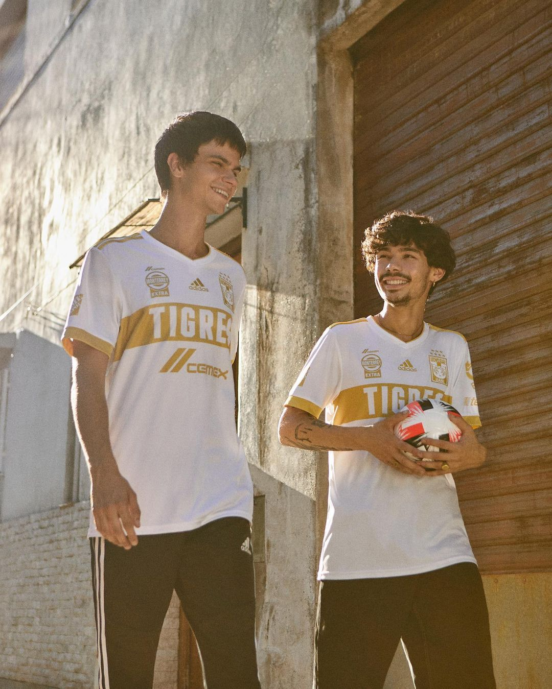 Two men walked down the street with a soccer ball in hand