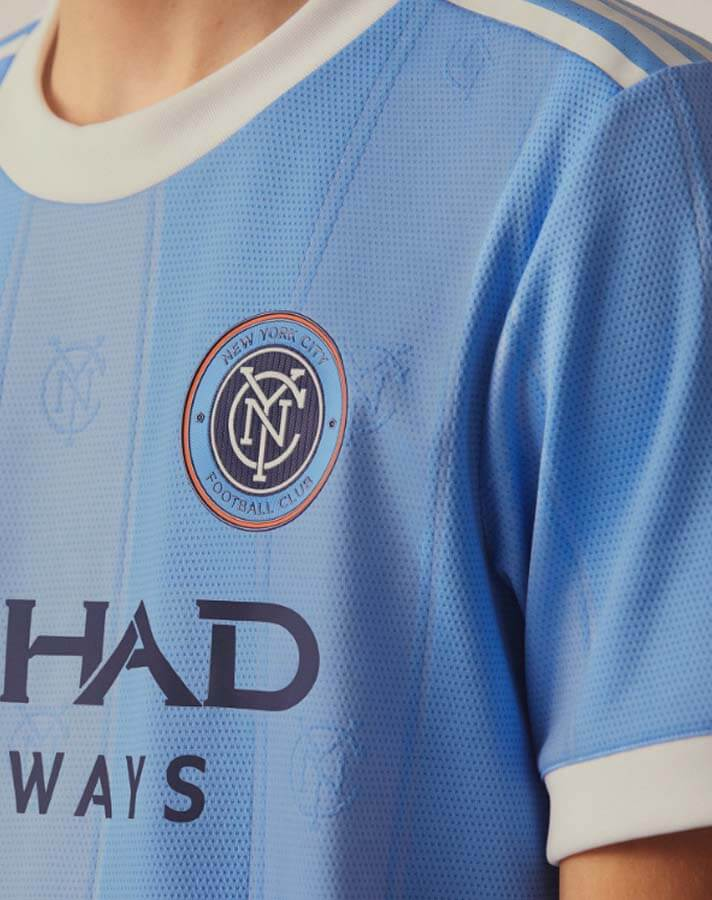 Light blue jersey with crest logo on chest