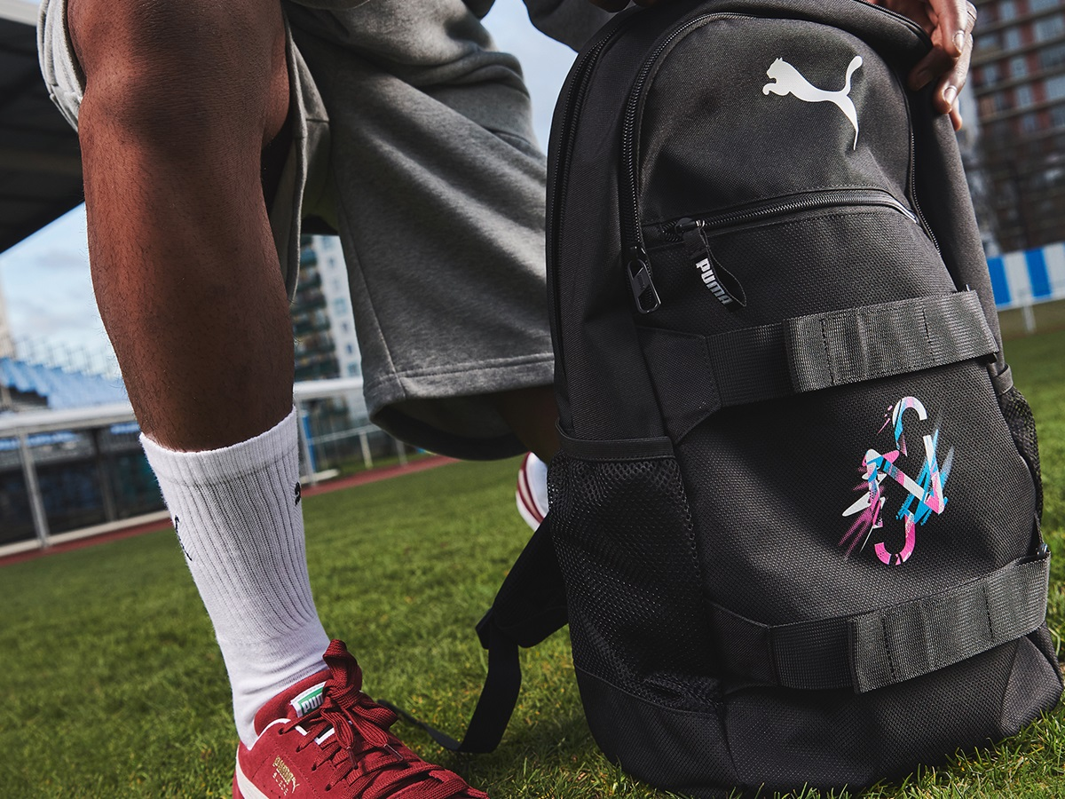 A black backpack sits on the pitch