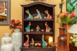 Assorted ceramic sculptures of ladies wearing colorful dresses