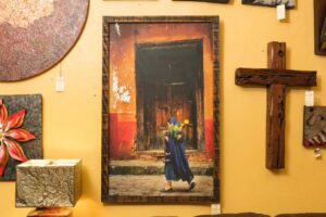Bruce Herman photograph of woman carrying flowers in front of a colorful wall and door