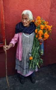 Bruce Herman photograph of elderly Mexican woman holding orange flowers