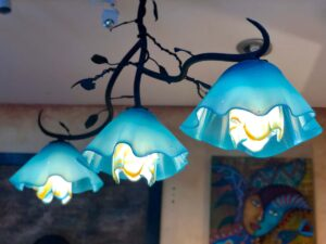 Wrought iron chandelier with three blue, flower-shaped blown glass shades