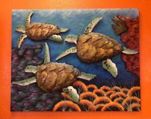 Metal wall art of turtles in the ocean