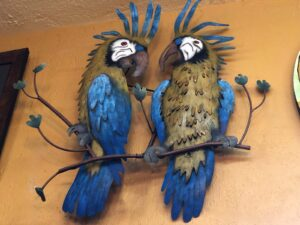 Colorful metal wall art of two toucans on a branch