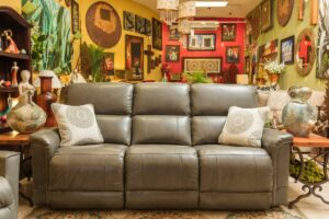 Gray reclining La-Z-Boy sofa with two decorative throw pillows, in Cabo San Lucas furniture showroom