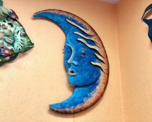Blue metal wall art piece of a moon with a face