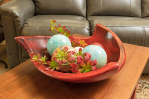 Red decorative ceramic bowl with ceramic spheres and faux florals