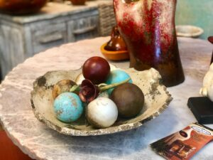 Decorative ceramic bowl with brown, white, blue, and red ceramic spheres and rose sitting on top of a coffee table
