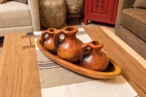Three ceramic pitchers in a decorative plate