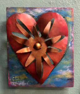 Small metal art piece of a heart with a sun in the center