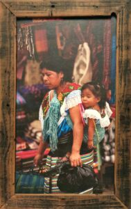 Bruce Herman photograph of Mexican woman carrying baby in a street market