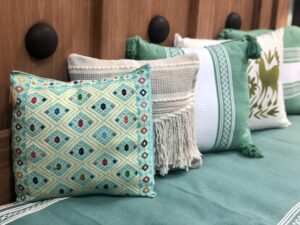 Four assorted Mexican embroidered pillows in shades of green and blue in Cabo San Lucas