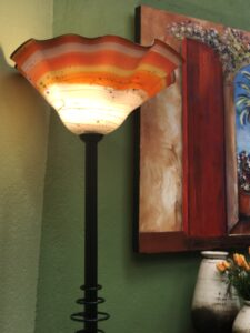 Orange and white blown glass floor lamp with iron stand, for sale at a furniture store in Cabo San Lucas, Mexico