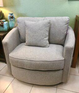 Light gray La-Z-Boy swivel chair with light gray throw pillow