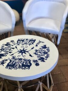 White Mexican equipal table with blue handpainted details in Cabo San Lucas, Mexico