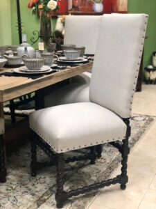 White upholstered chair with nailhead trim and elegant black base in Cabo San Lucas
