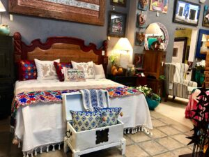Queen bed with Mexican handwoven bedspread, pillows, and a runner