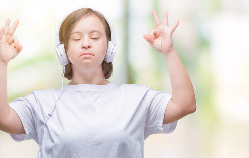Calm woman meditating with headphones on.