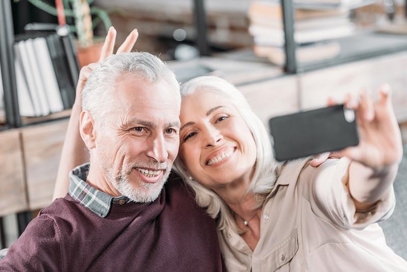 Happy Senior Couple Having Fun While Taking Selfie On Sofa