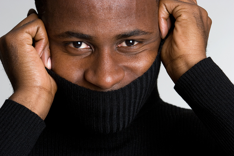 Man hiding smile with sweater