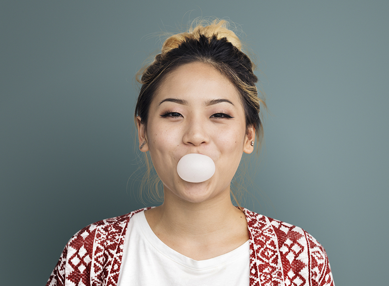 Woman Blowing a Bubble with Chewing Gum